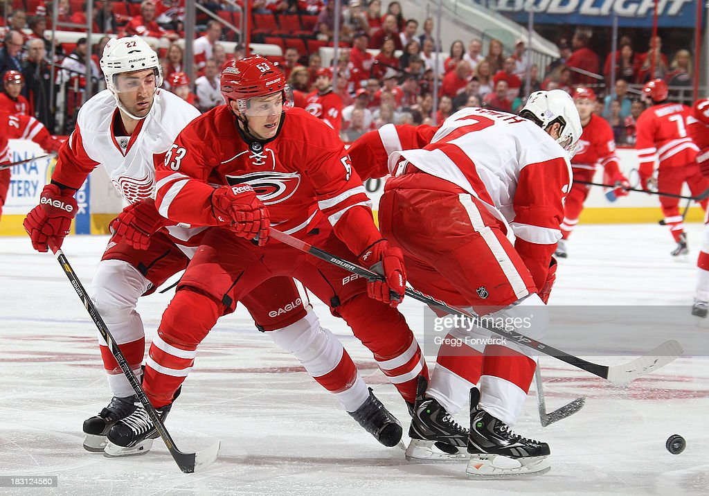 Jeff Skinner #53 of the Carolina Hurricanes battles for the puck between Brendan Smith #2 and Kyle Quincey #27 of the Detroit Red Wings on October 4, 2013 in the home opener at PNC Arena in Raleigh, North Carolina.
