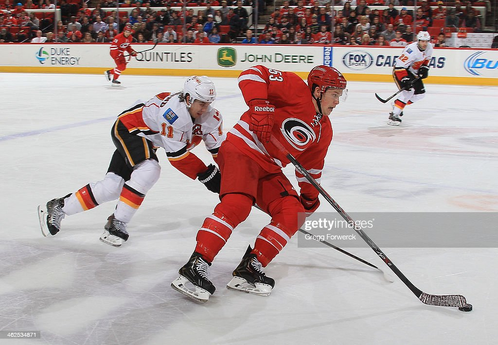 <a gi-track='captionPersonalityLinkClicked' href=/galleries/search?phrase=Jeff+Skinner&family=editorial&specificpeople=3147596 ng-click='$event.stopPropagation()'>Jeff Skinner</a> #53 of the Carolina Hurricanes carries the puck and is pursued by <a gi-track='captionPersonalityLinkClicked' href=/galleries/search?phrase=Mikael+Backlund&family=editorial&specificpeople=4324942 ng-click='$event.stopPropagation()'>Mikael Backlund</a> #11 of the Calgary Flames during their NHL game at PNC Arena on January 13, 2014 in Raleigh, North Carolina.