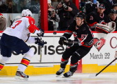 Jeff Skinner of the Carolina Hurricanes chases down a puck with Filip Kuba of the Florida Panthers during an NHL game on March 2 2013 at PNC Arena in...