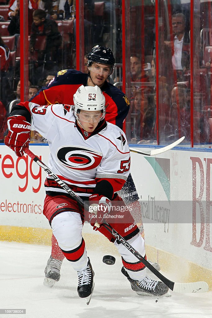 Jeff Skinner #53 of the Carolina Hurricanes digs the puck out from the boards Keaton Ellerby #4 of the Florida Panthers at the BB&T Center on January 19, 2013 in Sunrise, Florida.