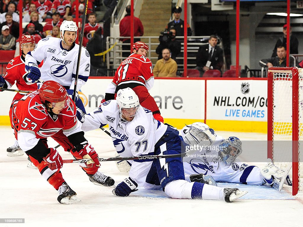 Jeff Skinner #53 of the Carolina Hurricanes flips the puck past Victor Hedman #77 and Mathieu Garon #32 of the Tampa Bay Lightning for a goal during the second period at PNC Arena on January 22, 2013 in Raleigh, North Carolina.