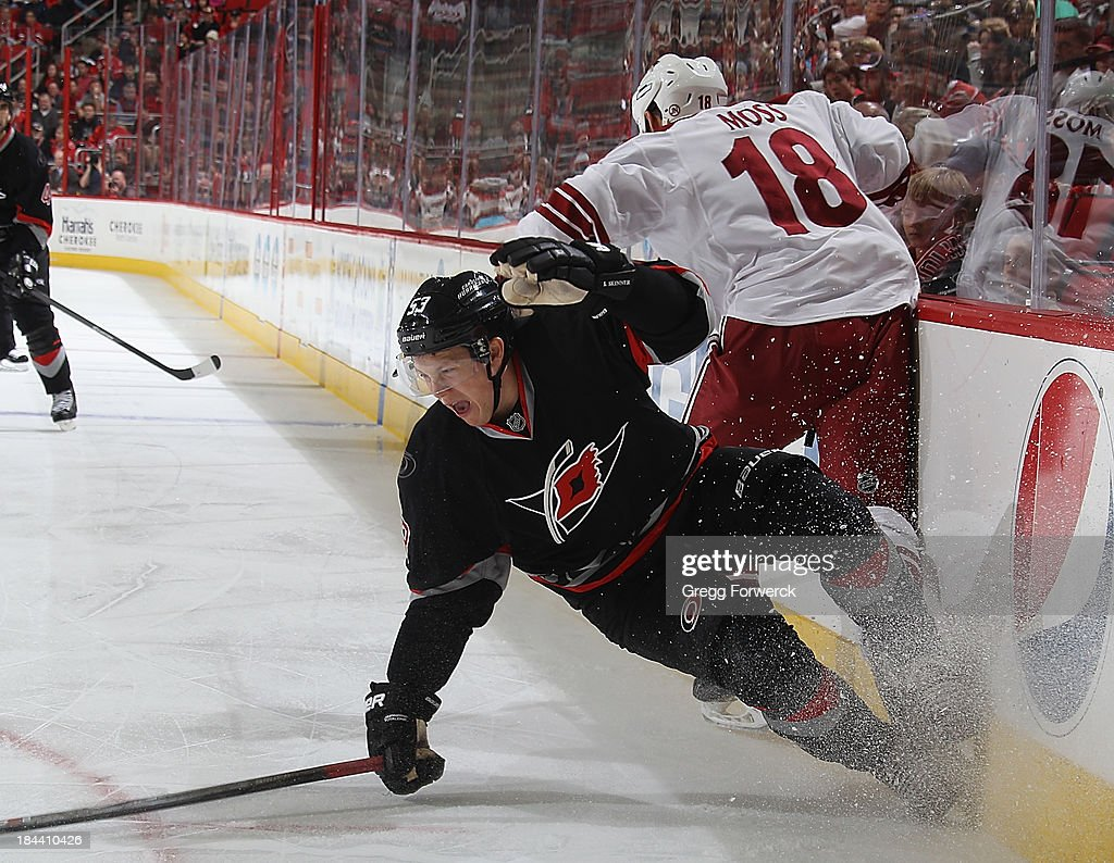 <a gi-track='captionPersonalityLinkClicked' href=/galleries/search?phrase=Jeff+Skinner&family=editorial&specificpeople=3147596 ng-click='$event.stopPropagation()'>Jeff Skinner</a> #53 of the Carolina Hurricanes goes down while battling along the boards against David Moss #18 of the Phoenix Coyotes during an NHL game at PNC Arena on October 13, 2013 in Raleigh, North Carolina.