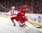 Jeff Skinner of the Carolina Hurricanes hits Brendan Smith of the Detroit Red Wings in the corner during an NHL game on April 11 2014 at Joe Louis...