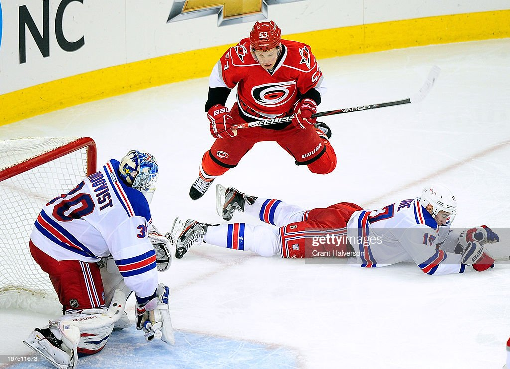 Jeff Skinner #52 of the Carolina Hurricanes hurdles John Moore #17 as he takes a shot against Henrik Lundqvist #30 of the New York Rangers during play at PNC Arena on April 25, 2013 in Raleigh, North Carolina. The Rangers won 4-3 in overtime.