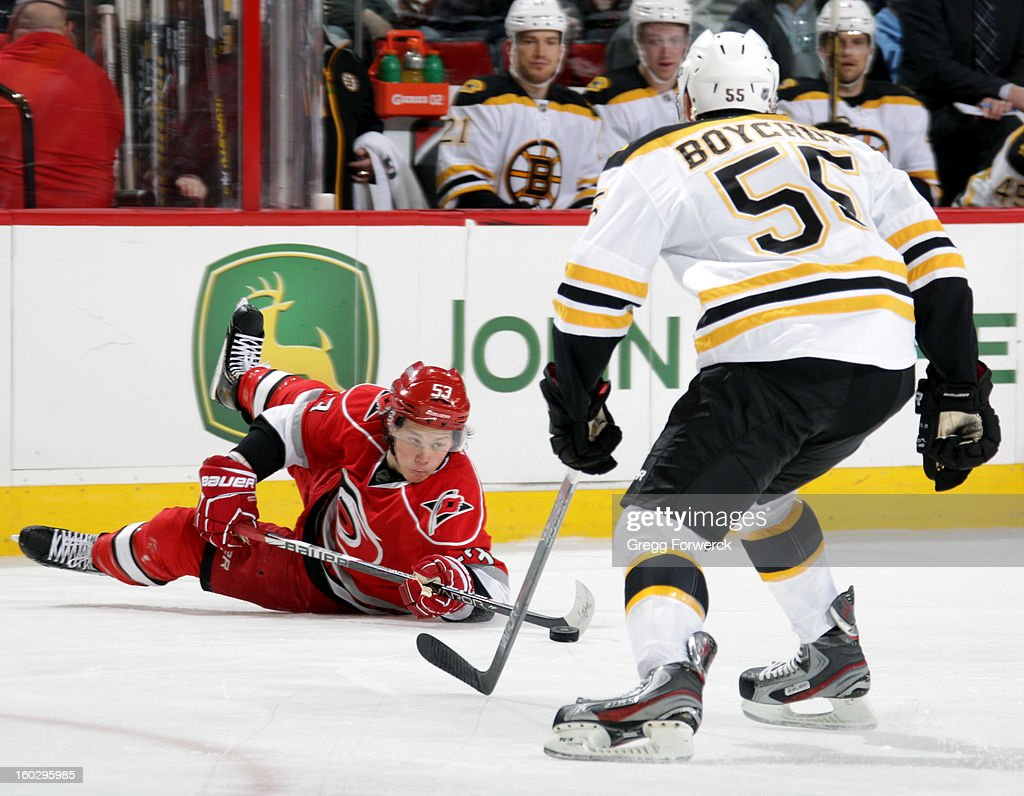 Jeff Skinner #53 of the Carolina Hurricanes makes an effort to play the puck from the ice as Johnny Boychuk #55 of the Boston Bruins closes in to defend during their NHL game on January 28, 2013 at PNC Arena in Raleigh North Carolina.