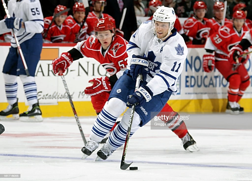 Jeff Skinner #53 of the Carolina Hurricanes races after Jay McClement #11 of the Toronto Maple Leafs as he handles the puck across the blue line during their NHL game at PNC Arena on February 14, 2013 in Raleigh, North Carolina.