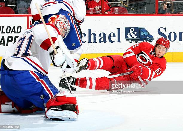 Jeff Skinner of the Carolina Hurricanes releases a shot while falling to the ice as Carey Price of the Montreal Canadiens blocks the puck during...