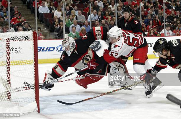 Jeff Skinner of the Carolina Hurricanes scores on goalie Corey Crawford of the Chicago Blackhawks as Brian Campbell of the Blackhawks reaches across...