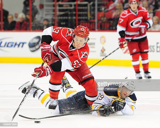 Jeff Skinner of the Carolina Hurricanes takes the puck away from Jason Pominville of the Buffalo Sabres during play at PNC Arena on January 24 2013...