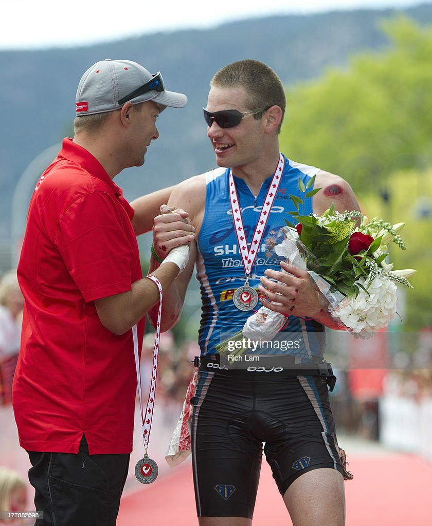 Jeff Symonds is congratulated by Challenge Family CEO Felix Walchshofer after winning the men's division of the Challenge Penticton Triathlon on August 25, 2013 in Penticton, British Columbia, Canada.