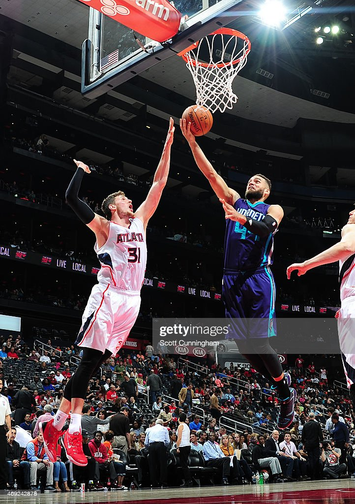 Jeff Taylor of the Charlotte Hornets goes for the layup against Mike Muscala of the Atlanta Hawks during the game on April 10 2015 at Philips Arena...