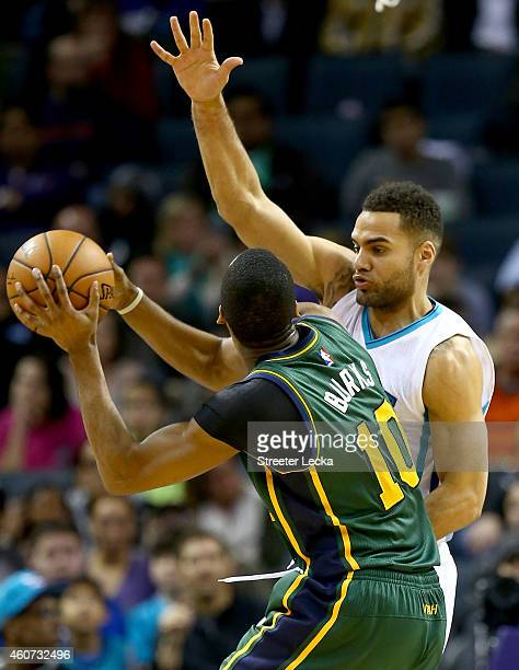 Jeff Taylor of the Charlotte Hornets guards Alec Burks of the Utah Jazz during their game at Time Warner Cable Arena on December 20 2014 in Charlotte...