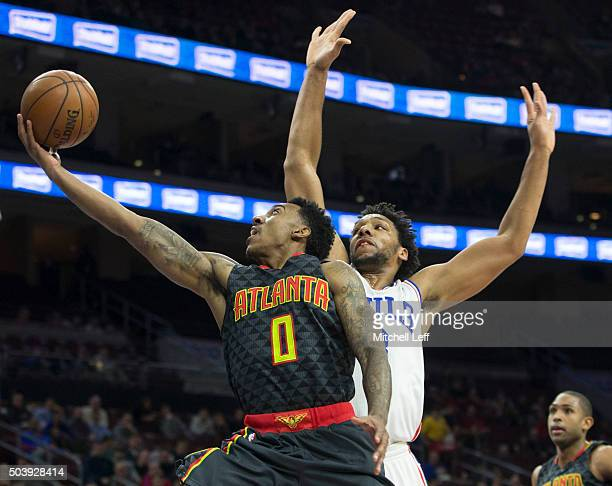 Jeff Teague of the Atlanta Hawks attempts a layup past Jahlil Okafor of the Philadelphia 76ers on January 7 2016 at the Wells Fargo Center in...