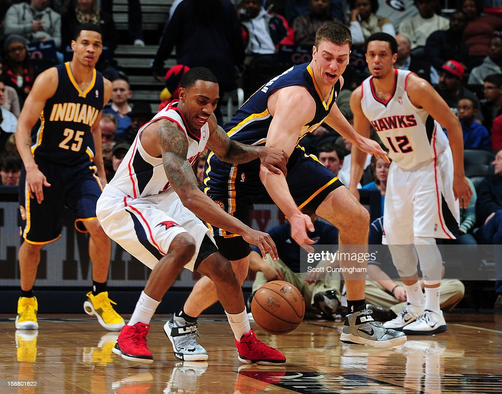 Jeff Teague #0 of the Atlanta Hawks battles for a loose ball against Tyler Hansbrough #50 of the Indiana Pacers on December 29, 2012 at Philips Arena in Atlanta, Georgia.