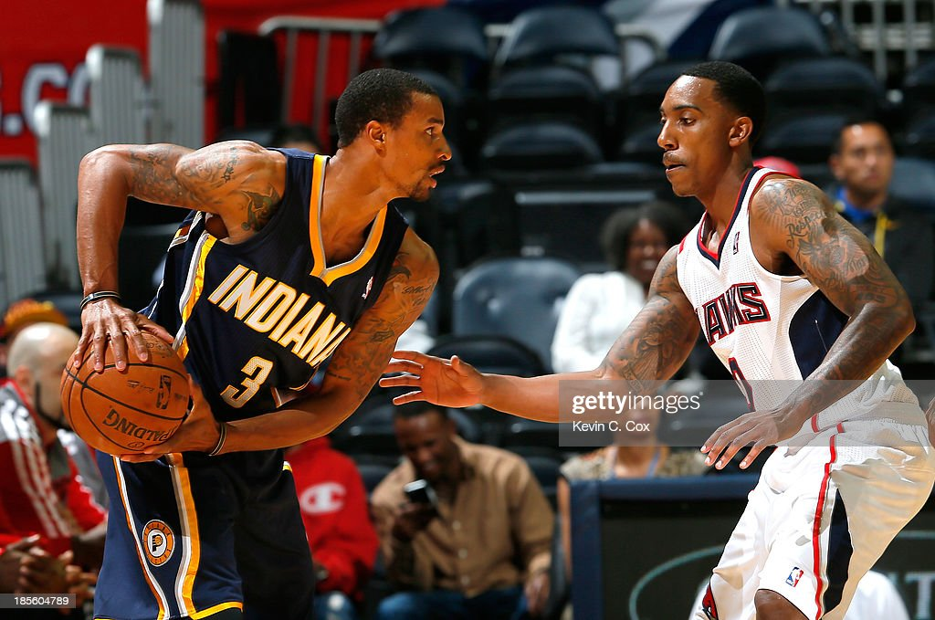 Jeff Teague #0 of the Atlanta Hawks defends against George Hill #3 of the Indiana Pacers at Philips Arena on October 22, 2013 in Atlanta, Georgia.