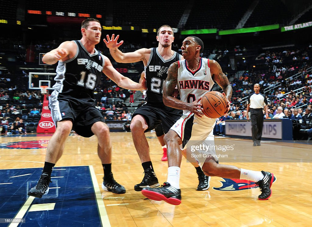<a gi-track='captionPersonalityLinkClicked' href=/galleries/search?phrase=Jeff+Teague&family=editorial&specificpeople=4680498 ng-click='$event.stopPropagation()'>Jeff Teague</a> #0 of the Atlanta Hawks drives to the basket against <a gi-track='captionPersonalityLinkClicked' href=/galleries/search?phrase=Aron+Baynes&family=editorial&specificpeople=2095512 ng-click='$event.stopPropagation()'>Aron Baynes</a> #16 and Nando de Colo #25 of the San Antonio Spurs on October 17, 2013 at Philips Arena in Atlanta, Georgia.