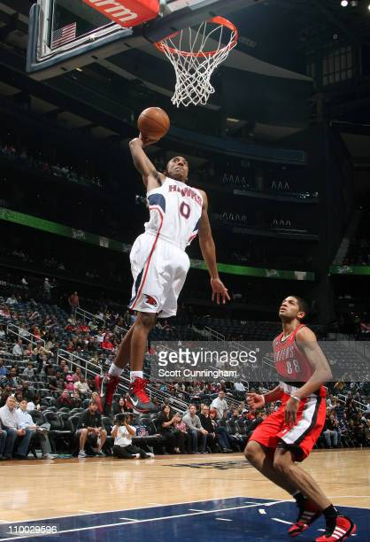 Jeff Teague of the Atlanta Hawks dunks against Nicolas Batum of the Portland Trail Blazers on March 12 2011 at Philips Arena in Atlanta Georgia NOTE...