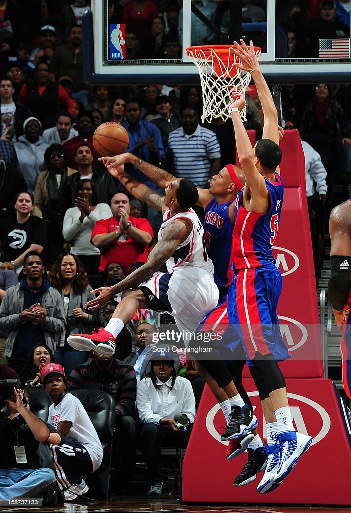 Jeff Teague #0 of the Atlanta Hawks goes to the basket against Charlie Villanueva #31 and Austin Daye #5 of the Detroit Pistons on December 26, 2012 at Philips Arena in Atlanta, Georgia.