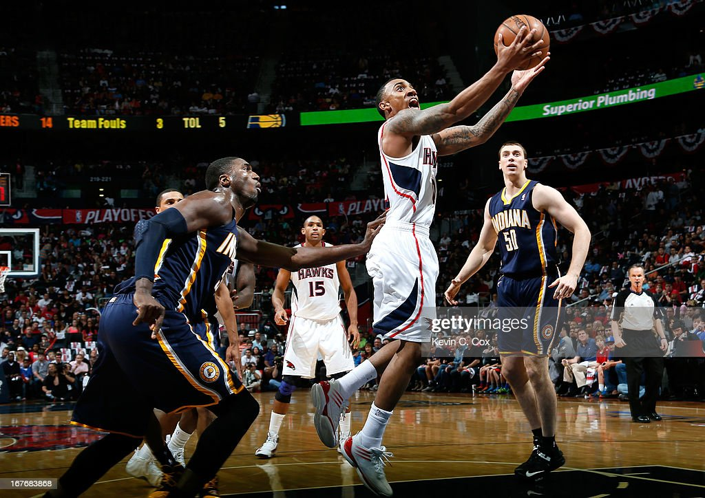 Jeff Teague #0 of the Atlanta Hawks lays in a basket past Roy Hibbert #55 of the Indiana Pacers during Game Three of the Eastern Conference Quarterfinals of the 2013 NBA Playoffs at Philips Arena on April 27, 2013 in Atlanta, Georgia.