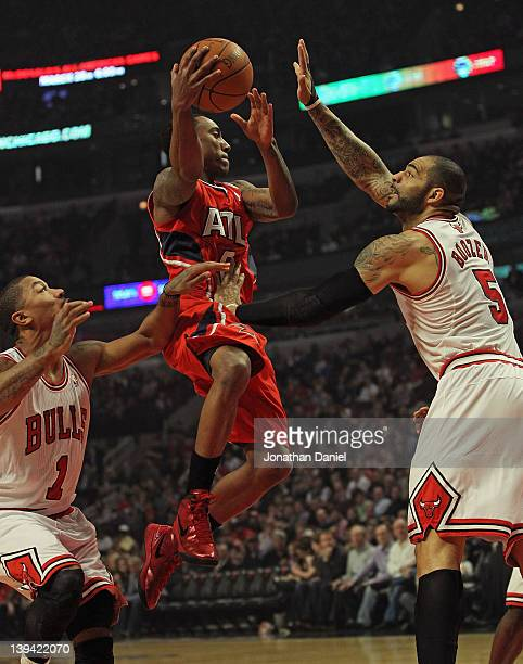 Jeff Teague of the Atlanta Hawks leaps to pass between Derrick Rose and Carlos Boozer of the Chicago Bulls at the United Center on February 20 2012...