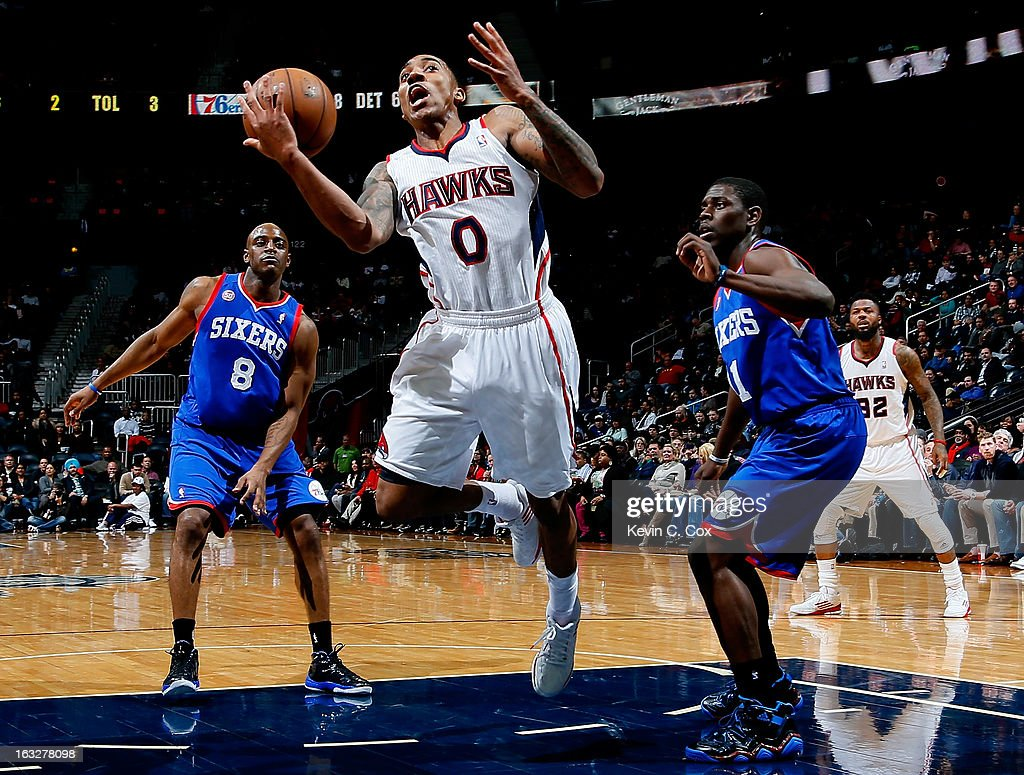 Jeff Teague #0 of the Atlanta Hawks loses the ball as he drives between Damien Wilkins #8 and Jrue Holiday #11 of the Philadelphia 76ers at Philips Arena on March 6, 2013 in Atlanta, Georgia.