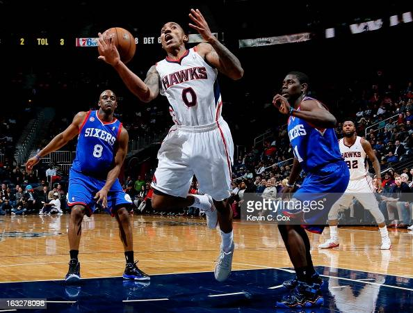 Jeff Teague of the Atlanta Hawks loses the ball as he drives between Damien Wilkins and Jrue Holiday of the Philadelphia 76ers at Philips Arena on...