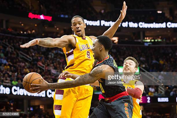 Jeff Teague of the Atlanta Hawks passes around Channing Frye and Matthew Dellavedova of the Cleveland Cavaliers during the second half at Quicken...