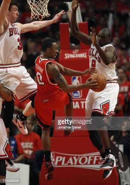 Jeff Teague of the Atlanta Hawks passes the ball between Omer Asik and Loul Deng of the Chicago Bulls in Game Five of the Eastern Conference...