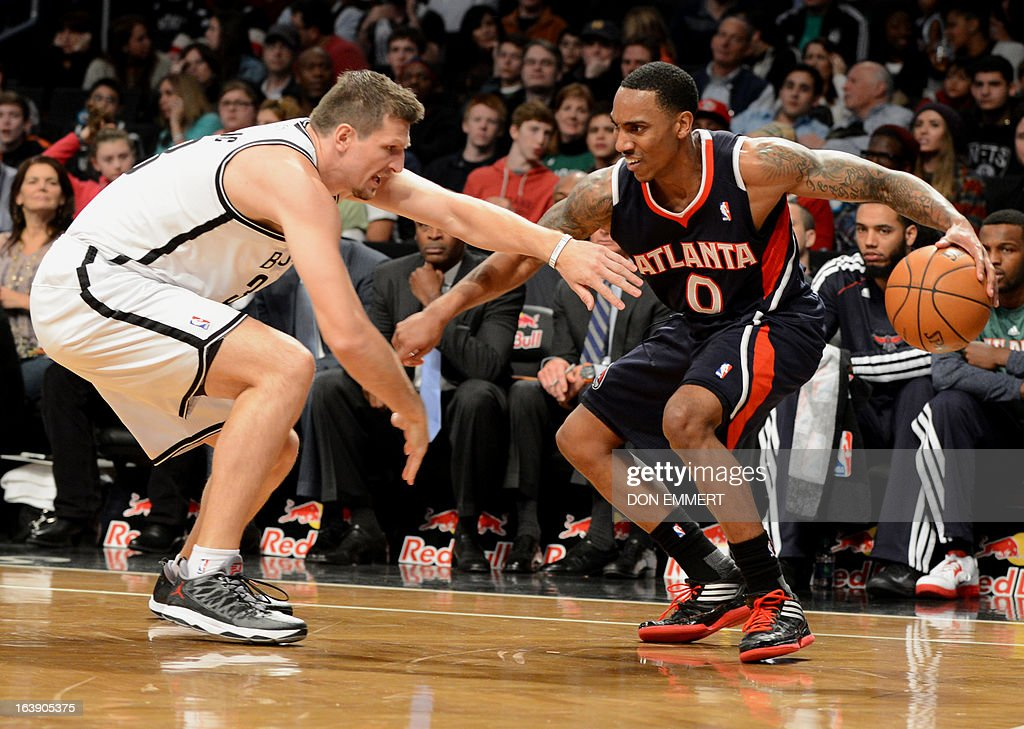 Jeff Teague (R) of the Atlanta Hawks protects the ball from Brooklyn Nets Mirza Teletovic March 17, 2013 at the Barclay Center in New York.