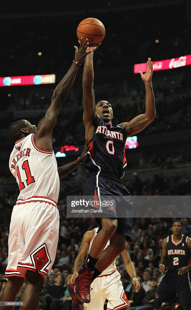 Jeff Teague #0 of the Atlanta Hawks puts up a shot over Ronnie Brewer #11 of the Chicago Bulls at the United Center on January 3, 2012 in Chicago, Illinois.