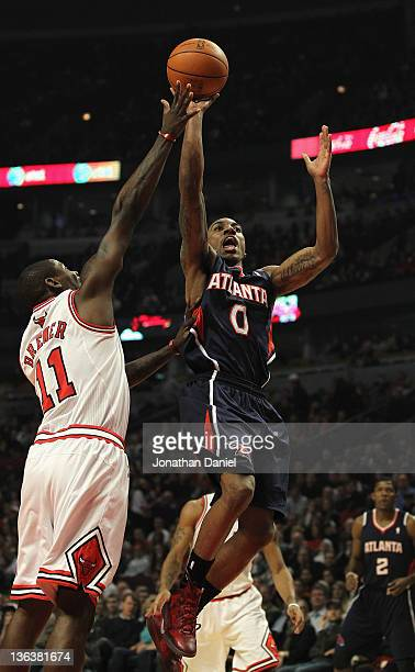 Jeff Teague of the Atlanta Hawks puts up a shot over Ronnie Brewer of the Chicago Bulls at the United Center on January 3 2012 in Chicago Illinois...
