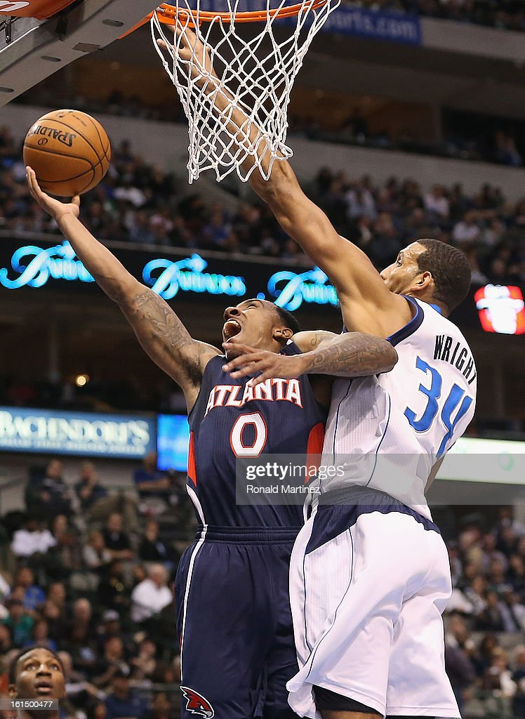 Jeff Teague #0 of the Atlanta Hawks takes a shot against Brandan Wright #34 of the Dallas Mavericks at American Airlines Center on February 11, 2013 in Dallas, Texas.