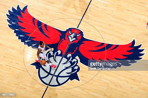 Jeff Teague of the Atlanta Hawks takes the ball up court across the Hawks logo during the game against the Orlando Magic on November 26 2013 at...