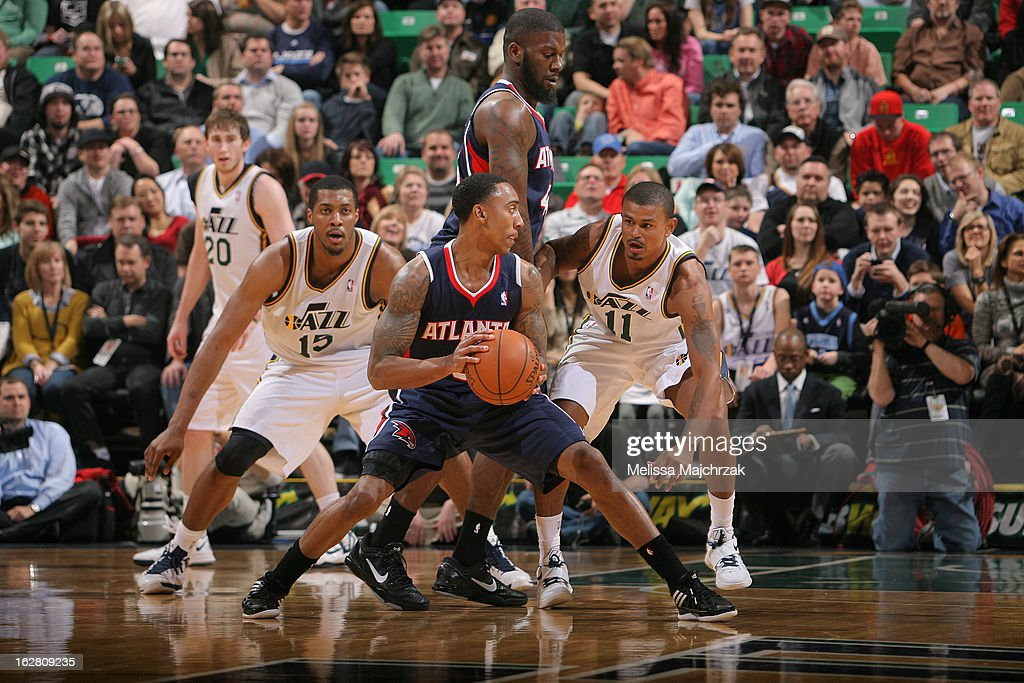 Jeff Teague #0 of the Atlantic Hawks gets help from teammate Ivan Johnson #44 to drive past Earl Watson #11 and Derrick Favors #15 of the Utah Jazz at Energy Solutions Arena on February 27, 2013 in Salt Lake City, Utah.