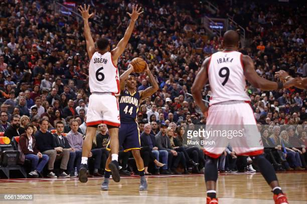 Jeff Teague of the Indiana Pacers passes the ball around Cory Joseph of the Toronto Raptors on March 19 2017 at Air Canada Centre in Toronto Ontario...