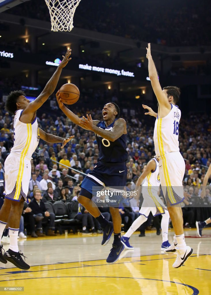 Jeff Teague #0 of the Minnesota Timberwolves goes up for a shot against Nick Young #6 and Omri Casspi #18 of the Golden State Warriors at ORACLE Arena on November 8, 2017 in Oakland, California.