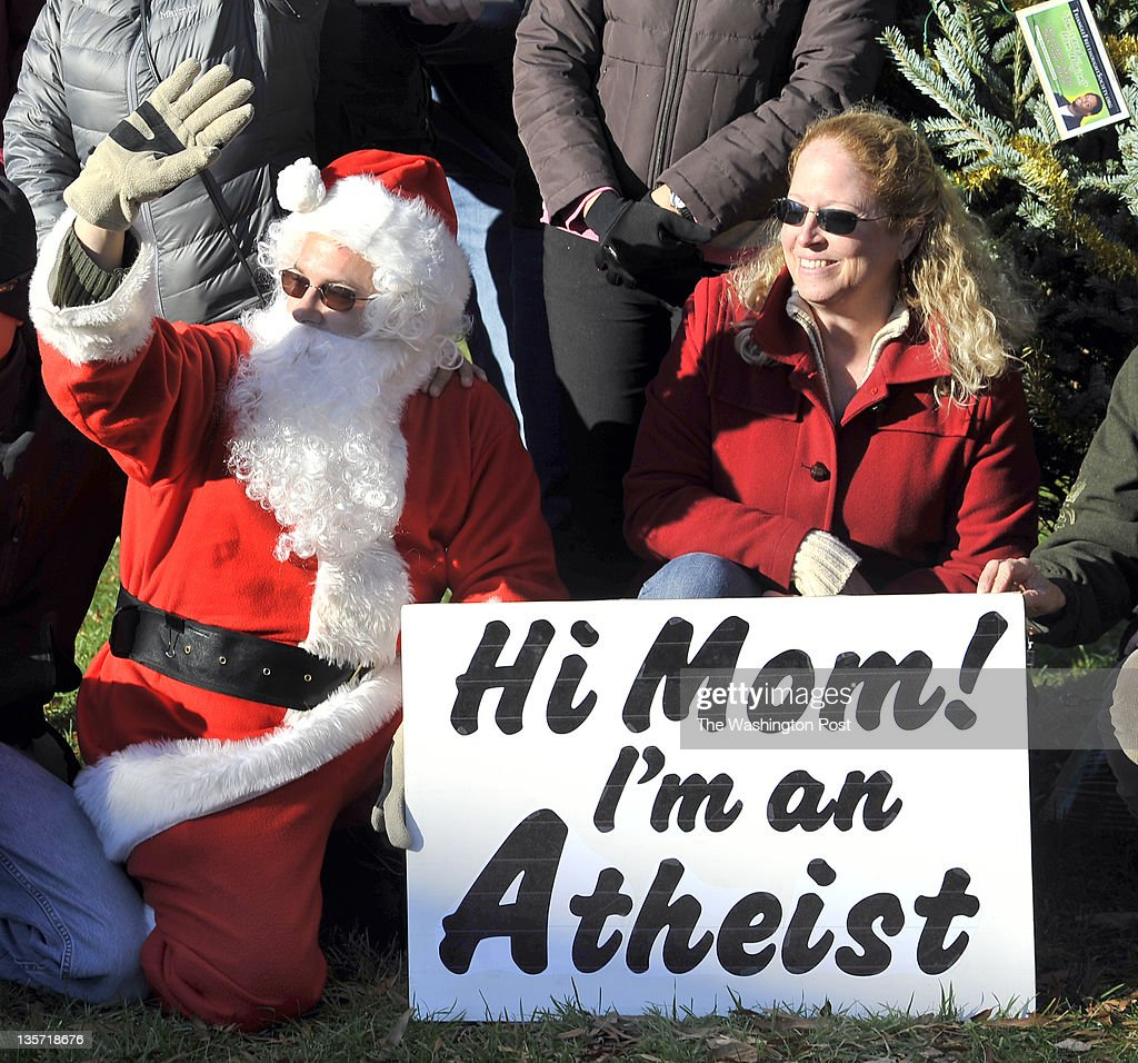 Jeff Wismer waved to the honking of a passing car as Ellen Birchlooked on as they posed with others in front of the atheist tree on the lawn of the...