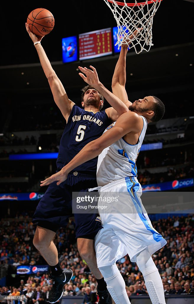 Jeff Withey of the New Orleans Pelicans takes a shot and is fouled by JaVale McGee of the Denver Nuggets at Pepsi Center on November 21 2014 in...