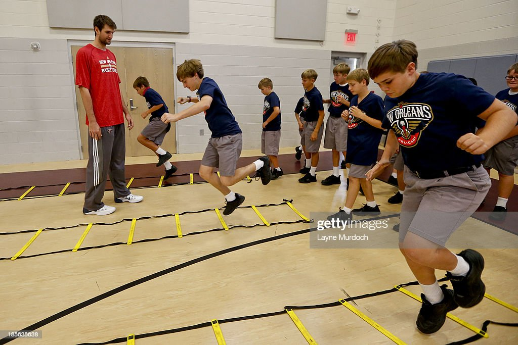 Jeff Withey of the New Orleans Pelicans works with students as the team partnered with Ochsner Health System, Blue Cross Blue Shield of Louisiana and the Louisiana Campaign for Tobacco-Free Living (TFL) celebrate the launch of the Pelicans Junior Training Camp program on October 21, 2013 at Christian Brothers School in New Orleans, Louisiana.