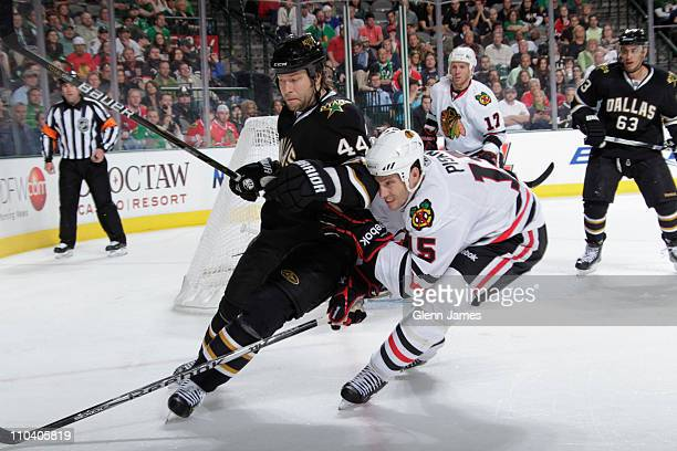 Jeff Woywitka of the Dallas Stars battles for position against Fernando Pisani of the Chicago Blackhawks at the American Airlines Center on March 17...