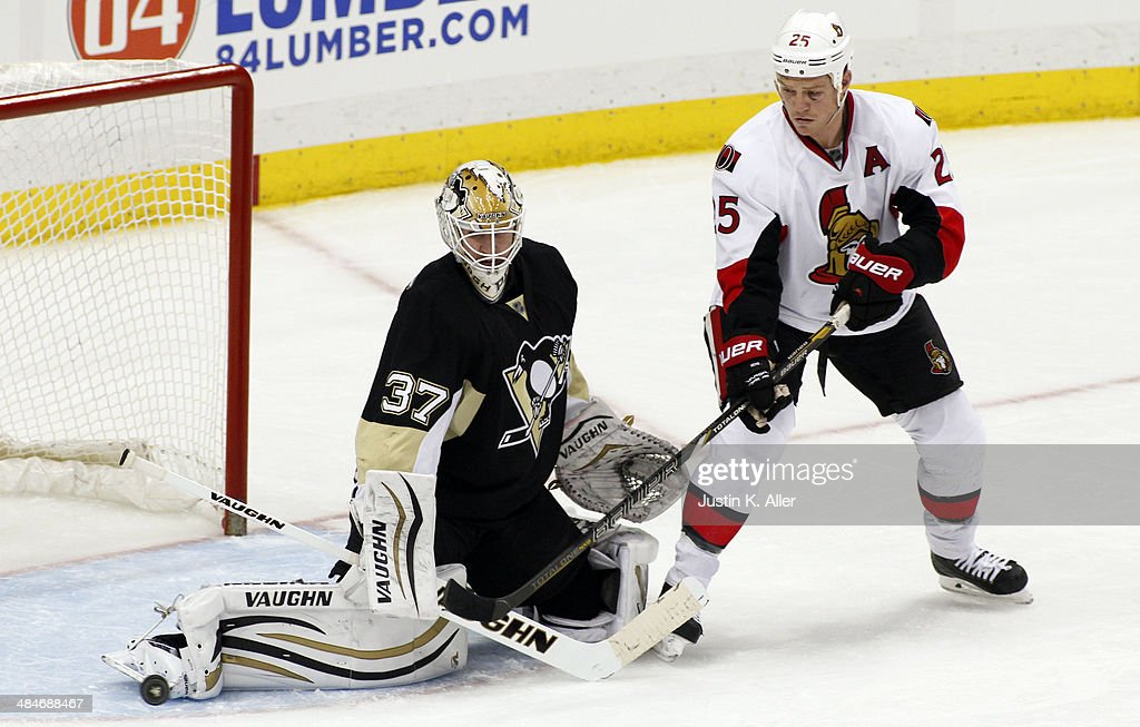 Jeff Zatkoff #37 of the Pittsburgh Penguins makes a save against Chris Neil #25 of the Ottawa Senators during the game at Consol Energy Center on April 13, 2014 in Pittsburgh, Pennsylvania. The Senators defeated the Penguins 3-2 in a shootout.