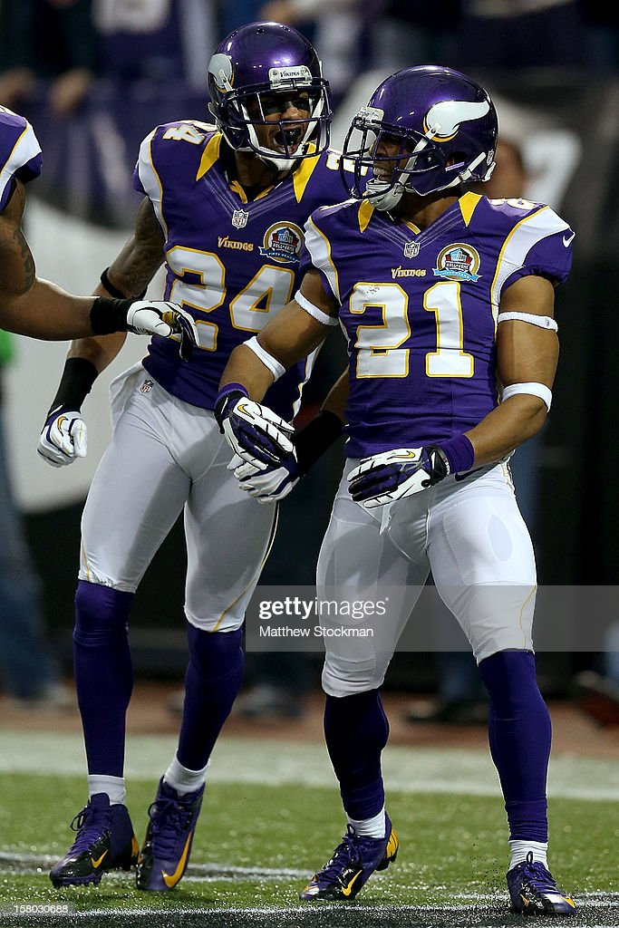 A.J. Jefferson #24 and Josh Robinson #21 of the Minnesota Vikings celebrate a Robinson interception against the Chicago Bears at Mall of America Field on December 9, 2012 in Minneapolis, Minnesota.