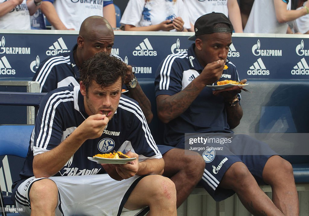 Jefferson Farfan of Schalke (R) and Tranquillo Barnetta eat spanish food after Raul's farewell match between Schalke 04 and Al-Sadd Sports Club Katar at Veltins Arena on July 27, 2013 in Gelsenkirchen, Germany.