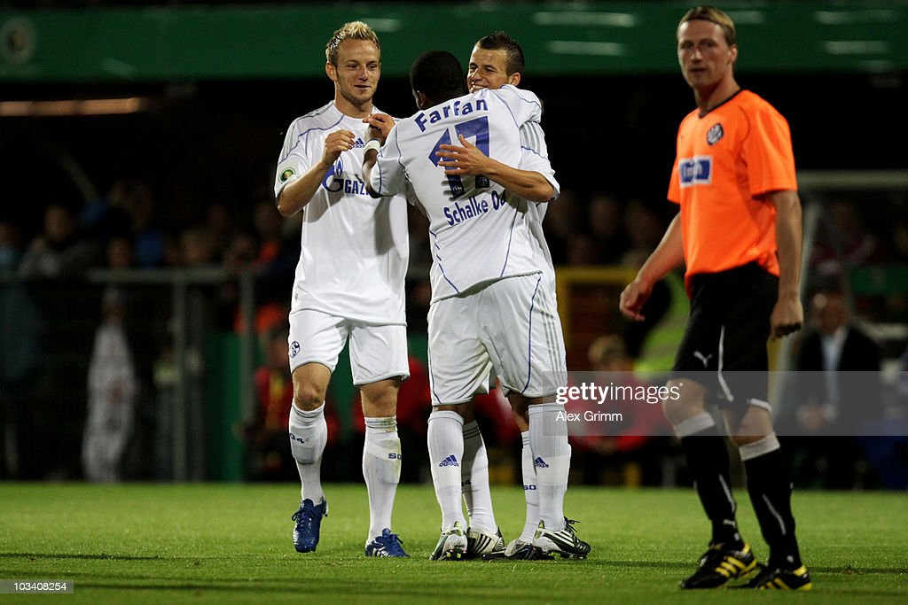 Jefferson Farfan of Schalke celebrates his team's second goal with team mates Ivan Rakitic (L) and Lukas Schmitz (back) as Thomas Scheuring of Aalen reacts during the DFB Cup first round match between VfR Aalen and FC Schalke 04 at the Scholz Arena on August 16, 2010 in Aalen, Germany.