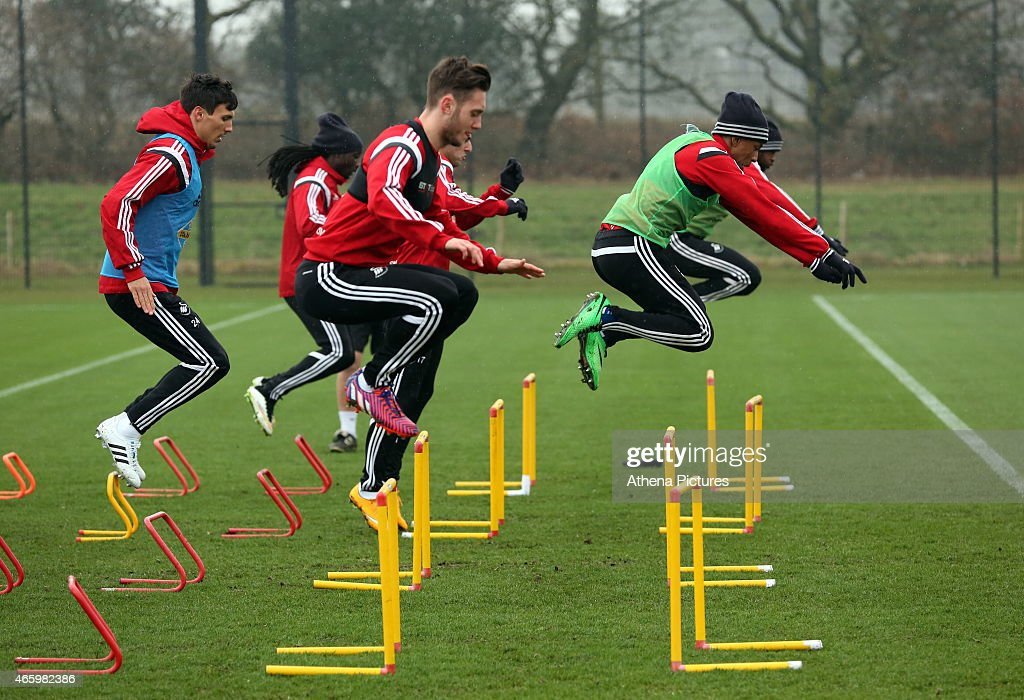 Jefferson Montero (R) jumps over a hurdle during the Swansea City training session at Fairwood Training Ground on March 12, 2015 in Swansea, Wales.