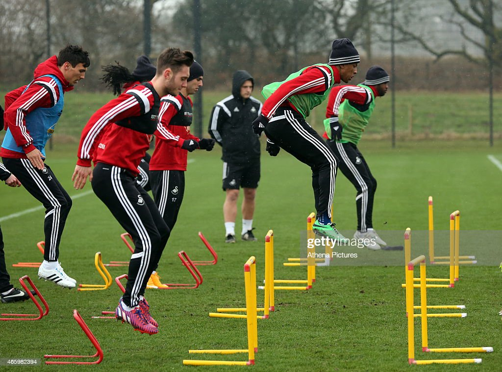 Jefferson Montero (2nd R) jumps over a hurdle during the Swansea City training session at Fairwood Training Ground on March 12, 2015 in Swansea, Wales.