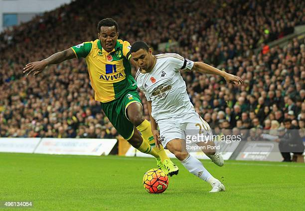 Jefferson Montero of Swansea City and Andre Wisdom of Norwich City compete for the ball during the Barclays Premier League match between Norwich City...