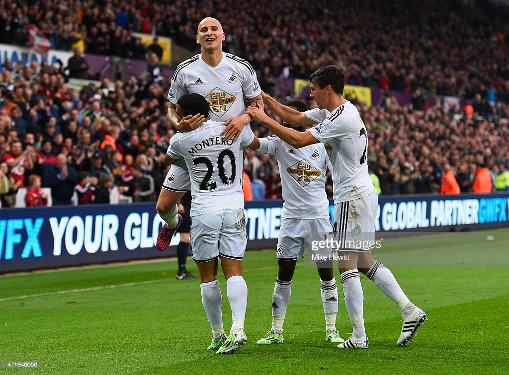 <a gi-track='captionPersonalityLinkClicked' href=/galleries/search?phrase=Jefferson+Montero&family=editorial&specificpeople=4406087 ng-click='$event.stopPropagation()'>Jefferson Montero</a> (1st L) of Swansea City celebrates scoring his team's first goal with his team mates <a gi-track='captionPersonalityLinkClicked' href=/galleries/search?phrase=Jonjo+Shelvey&family=editorial&specificpeople=4940315 ng-click='$event.stopPropagation()'>Jonjo Shelvey</a> (2nd L), <a gi-track='captionPersonalityLinkClicked' href=/galleries/search?phrase=Jack+Cork+-+Soccer+Player&family=editorial&specificpeople=4206991 ng-click='$event.stopPropagation()'>Jack Cork</a> (1st R) and <a gi-track='captionPersonalityLinkClicked' href=/galleries/search?phrase=Nathan+Dyer&family=editorial&specificpeople=684113 ng-click='$event.stopPropagation()'>Nathan Dyer</a> (2nd R) during the Barclays Premier League match between Swansea City and Stoke City at Liberty Stadium on May 2, 2015 in Swansea, Wales.