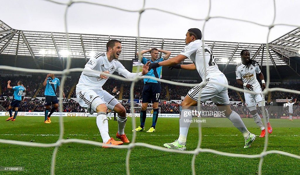Jefferson Montero (R) of Swansea City celebrates scoring his team's first goal with his team mates Gylfi Sigurdsson (C) and Marvin Emnes (L) during the Barclays Premier League match between Swansea City and Stoke City at Liberty Stadium on May 2, 2015 in Swansea, Wales.