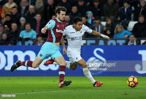 Jefferson Montero of Swansea City FC is challenged by Havard Nordtveit of West Ham United during the Premier League match between Swansea City and...